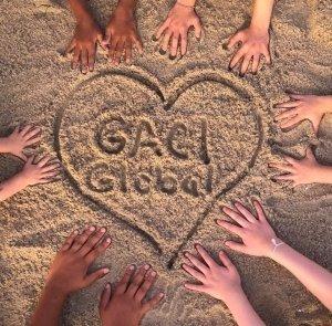 Hands around GACI Global drawn in the sand